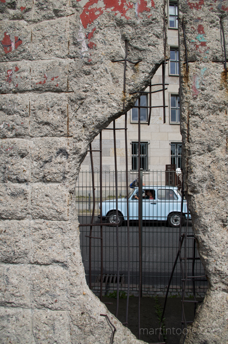 berlin wall with old car through crack