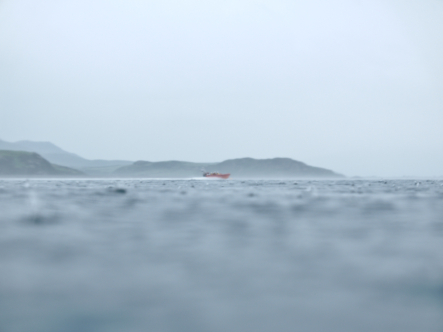 rnli boat on the water out at criccieth in a rain storm